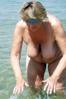 Naked old nudist at the beach. This aged bitch a..
