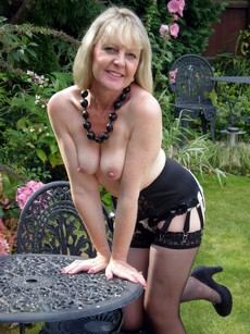 My charming mature wife posing topless in the..