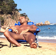 Tanned naked guy fell a sleep in a chaise longue