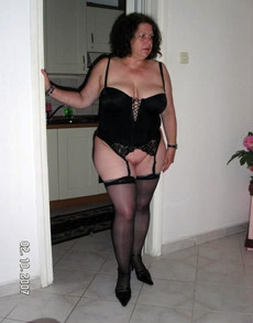 Brunette wife in black corset shows off her..